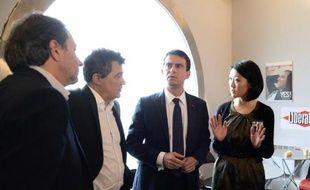 Le Premier ministre Manuel Valls (c), la ministre de la Culture Fleur Pellerin (d) et le chroniqueur de Charlie Hebdo Patrick Pelloux (2e g) au siège de Libération à Paris le 9 janvier 2015