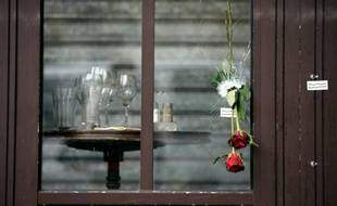 """Des roses glissées dans les impacts de balle sur la vitrine de la """"Bonne Bière"""" en hommage aux victimes, le 17 novembre 2015 à Paris"""