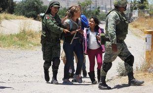 Des membres de la garde nationale mexicaine arrêtent des migrants qui tentaient de franchir le Rio Bravo, à Ciudad Juarez.