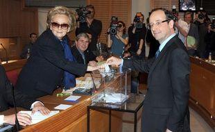 Le député socialiste François Hollande, s'apprête à déposer son  bulletin de vote dans l'urne, sous le regard de Bernadette Chirac, le 31 mars 2011 à  l'Hôtel du département de Tulle, en Corrèze.