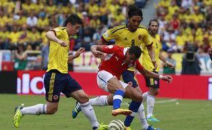 Les Colombiens James Rodriguez (à gauche) et Abel Aguilar prennent en tenaille le Chilien Alexis Sanchez, le 11 octobre 2013 à Barranquilla, lors d'un match éliminatoire pour la Coupe du monde 2014.