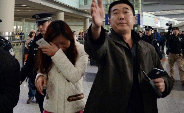 Une femme en pleurs est escortée vers un bus affrété pour les proches des personnes disparues à bord du vol Kuala Lumpur-Pékin, à l'aéroport de Pékin le 8 mars 2014