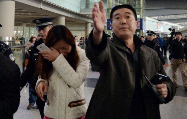 Une femme dont le proche est porté disparu dans le Boeing 777-200 de Malaysia Airlines pleure à l'aéroport de Pékin le 8 mars 2014