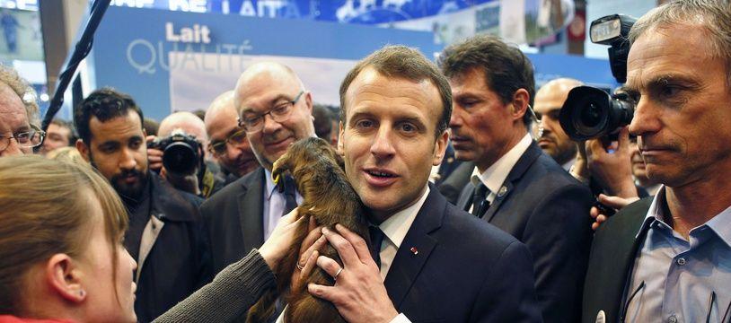 Emmanuel Macron et la poule Agathe, offerte lors de sa visite du 55e Salon de l'agriculture, à Paris, le 24 février 2018.