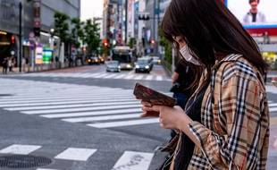 Une femme, suspendue à son téléphone, se promène dans la rue à Tokyo