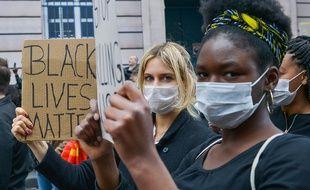 Des manifestants à Paris, pour dénoncer les violences policières en France, brandissant des pancartes Black Lives Matter.