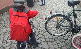 Un enfant à vélo portant un casque devant une école du centre de Strasbourg