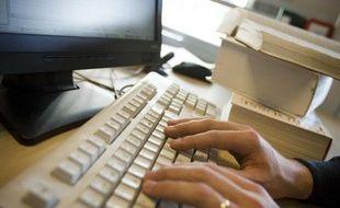Un homme pianote sur un clavier d'ordinateur.