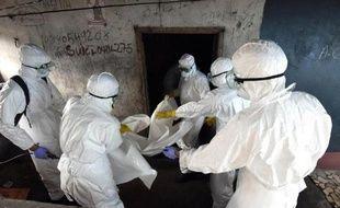 Des membres de la Croix rouge s'apprêtent à emmener le corps d'un homme mort probablement du virus Ebola, à Monrovia, dans la capitale du Liberia, le 4 octobre 2014