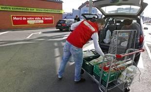Un employé de Chrono Drive charge la voiture d'une cliente près de Lille.