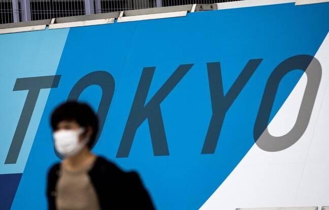 648x415 personne masquee devant logo jeux olympiques 2020