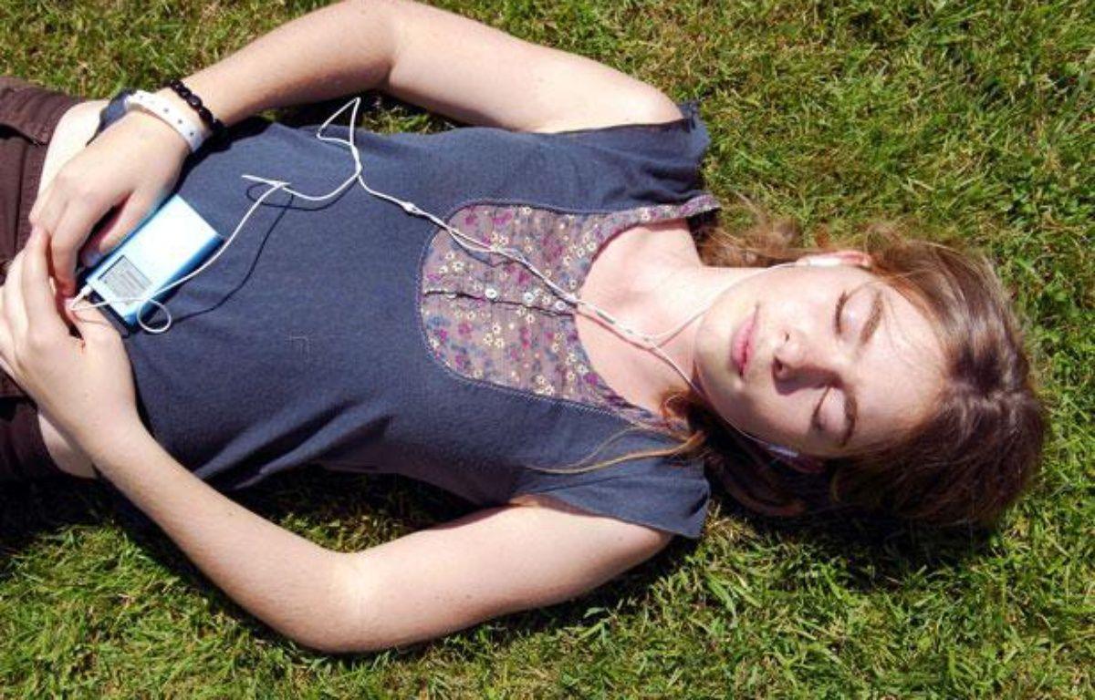 Une jeune fille écoute de la musique au casque, dans l'herbe, à la cool. – CAPMAN VINCENT/SIPA