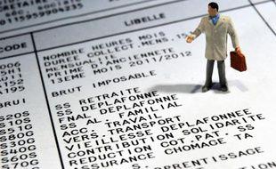 Photo d'une figurine posée sur un bulletin de salaire