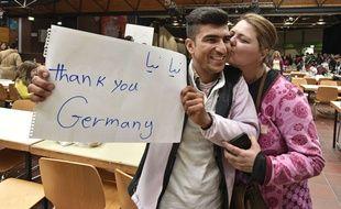 Un réfugié venu d'Afghanistan accueilli par un baiser et brandissant une bannière «Merci, l'Allemagne» à son arrivée à Dortmund, en train, le dimanche 6 septembre 2015.