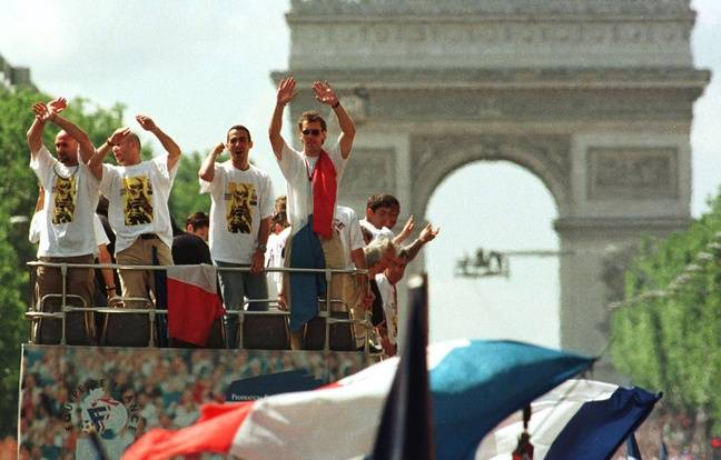 Teammates of the victorious French World Cup soccer team, from left: Fabien Barthez, Vincent Candela, Youri Djorkaeff and Laurent Blanc standing at the top of a bus parade on the Champs Elysees in Paris, France on Monday July 13, 1998 after their 3-0 victory over Brazil July 12 in the final of the World Cup.