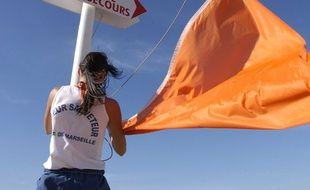 Une maître nageur sauveteur hisse le drapeau orange sur une plage de Marseille.
