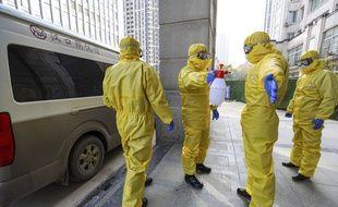 Des employés de pompes funèbres se désinfectent le 30 janvier à Wuhan après s'être occupés d'une victime du Covid-19.