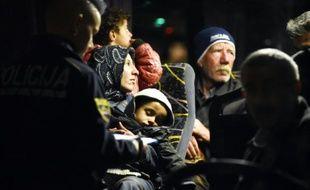 Des policiers solvènes enregistrent les migrants à  bord d'un bus le 21 octobre 2015 à Brezice en Solvénie