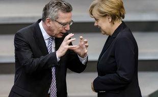 Le ministre allemand de l'Intérieur Thomas de Maiziere (L), en discussion avec la chancelière allemande Angela Merkel lors d'une session plénière à la Chambre basse du Parlement le 3 juillet 2014 à Berlin avant que les législateurs allemands votent un projet de loi pour un salaire minimum national.