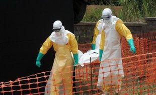 Des membres de l'organisation Médecins sans frontières (MSF) transportent le corps d'un malade décédé du virus Ebola, le 1er avril 2014 à Guekedou, en Guinée