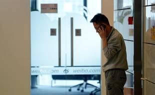 Un employé chinois de l'entreprise Sina Weibo s'isole pour téléphoner dans un couloir.