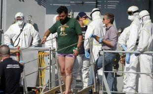 Un homme suspecté d'être un passeur quitte un bateau d ela marine irlandaise à Palerme en Italie, le 6 août 2015