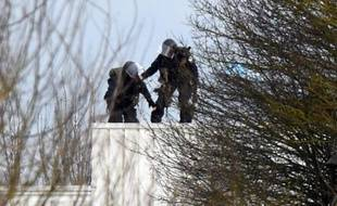 Des policiers prennent position sur le toit où sont retranchés les deux preneurs d'otage, auteurs présumés de la tuerie à Charlie hebdo, le 9 janvier 2015 à Dammartin-en-Goële, enSeine-et-Marne
