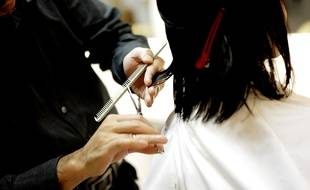 Un coiffeur coupant les cheveux d'une cliente. Image d'illustration.