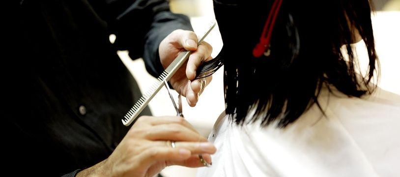 Un coiffeur coupant les cheveux d'une cliente (illustration).