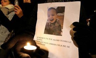 Reims (Marne), le 30 novembre 2016. Une femme tient une photo du petit Tony, lors d'une marche blanche en sa mémoire.