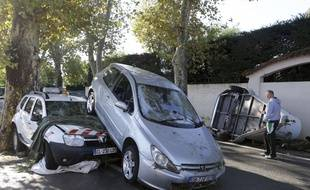 A man walks past damaged cars in Biot, near Cannes, southeastern France, Sunday Oct.4, 2015. Sudden heavy rains around the French Riviera have killed at least 10 people, including some trapped in cars, a campsite and a retirement home, and left six missing. Car and train traffic was disrupted along the Mediterranean coast. (AP Photo/Lionel Cironneau)/NIC103/774647984835/1510041138