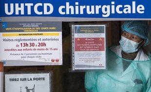 Rennes, le 1er avril. Une femme équipée d'un masque et d'une blouse regarde un patient infecté par le coronavirus à travers une vitre.