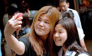 Deux étudiantes font un selfie à Bangkok, en 2014.