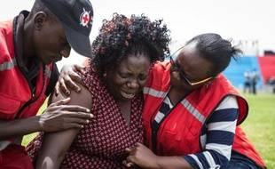 Des membres de la Croix-Rouge aident, le 5 avril 2015 à Nairobi, dans le stade Nyayo, une femme venant d'apprendre que l'un de ses proches fait partie des personnes tuées par les shebab à l'université de Garissa