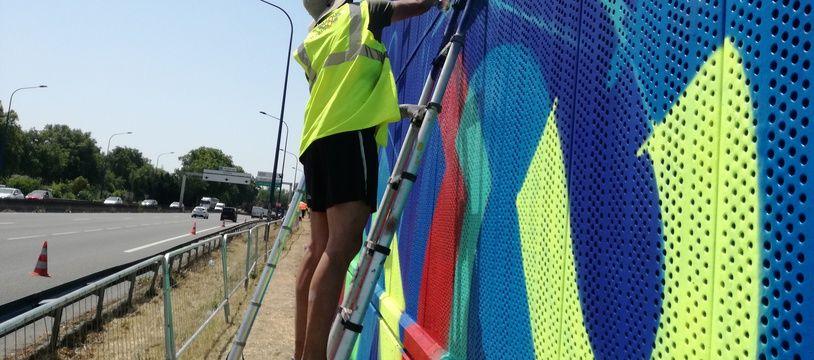 Le graffiti artiste toulousain Soone en train de travailler sur un mur du périphérique toulousain.