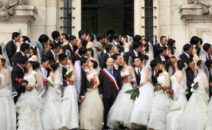 Photo du 7 mai 2009 montrant un groupe de couples chinois posant avec l'ancien maire de Tours Jean Germain devant la mairie de Tours