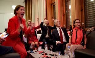 Le candidat travailliste Jonas Gahr Store (2e à droite) réagit aux premières projections de sortie des urnes, lundi 13 septembre.