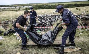 Des secouristes ukrainiens lèvent un corps sur le site du crash du vol MH 17 à Grabove, près de Donetsk en Ukraine le 20 juillet 2014