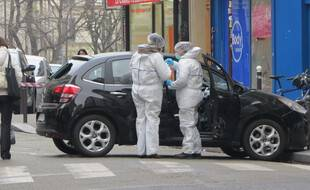 Des enquêteurs de la police scientifique et judiciaire enquêtent sur la voiture laissée par les auteurs de la fusillade de Charlie Hebdo le 7 janvier 2015.