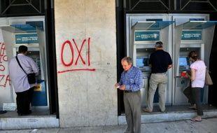 """Un graffiti """"NON"""" a été inscrit sur la façade d'une banque, tandis que des grecs retirent de l'argent dans les distibuteurs, le 2 juillet 2015 à Thessalonik"""