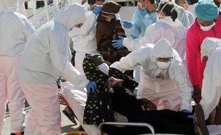 Des migrantes débarquent d'un bateau pour recevoir des soins après une opération de sauvetage, le 15 septembre 2014 à Brindisi, en Sicile