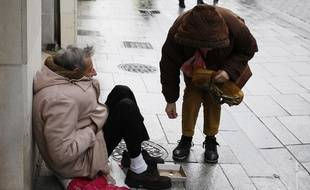 Une femme donne à un homme sans-abri.