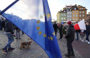 Des gens brandissent des drapeaux de l'Union européenne et de la Pologne lors d'une manifestation à Varsovie, en Pologne, le dimanche 10 octobre 2021.