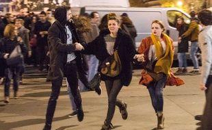 Des personnes fuient en courant la place de la République, à Paris, après qu'un mouvement de foule, lié à une fausse alerte, est survenu, le 15 novembre 2015.
