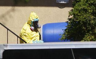 Un homme se débarrasse d'un tonneau bleu de l'appartement à Dallas où Thomas Eric Duncan est resté après avoir voyagé du Liberia au Texas, le 3 octobre 2014.
