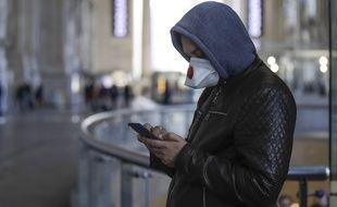 Un homme utilisant son smartphone durant la crise du coronavirus (illustration).