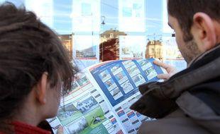 Jeune couple à la recherche d'un bien immobilier, consultant les annonces d'une agence.