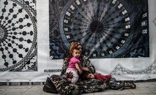 Une réfugiée syrienne mendie avec son enfant dans une rue d'Istanbul, le 16 juillet 2014