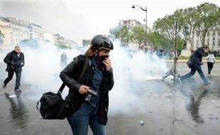 Les manifestants tentent d'échapper au nuage de gaz lacrymo lors des manifestations contre la loi Travail, à Paris le 12 mai 2016