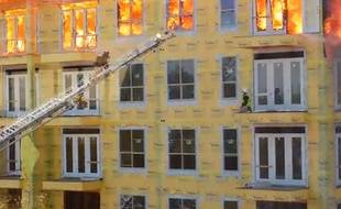Capture d'écran d'un immeuble en feu, menaçant un ouvrier sur le rebord de la fenêtre